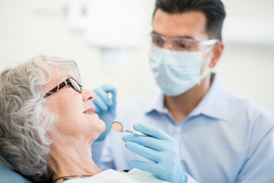 An elderly woman receiving a dental exam from her oral surgeon.